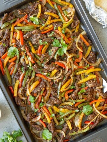 Overhead closeup view of cooked sliced beef, peppers and onions in a sheet pan.