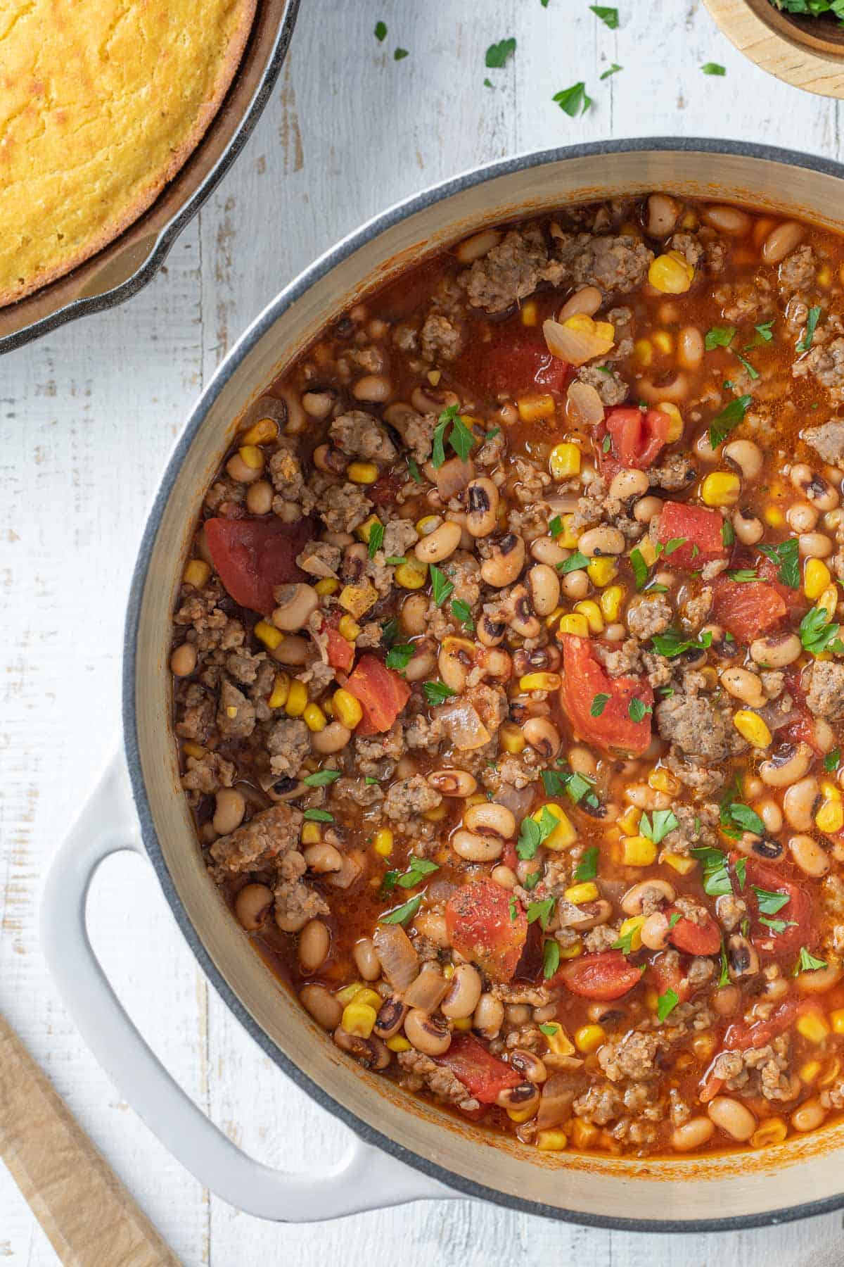 Overhead closeup view of black-eyed pea and sausage stew in a white Dutch oven.