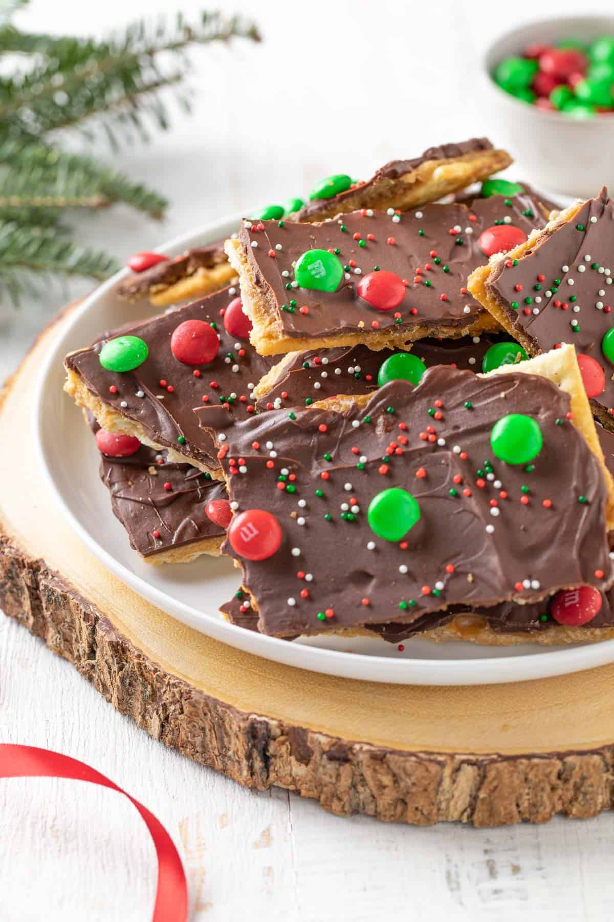 Closeup view of Christmas crack topped with red and green candy on a white plate.