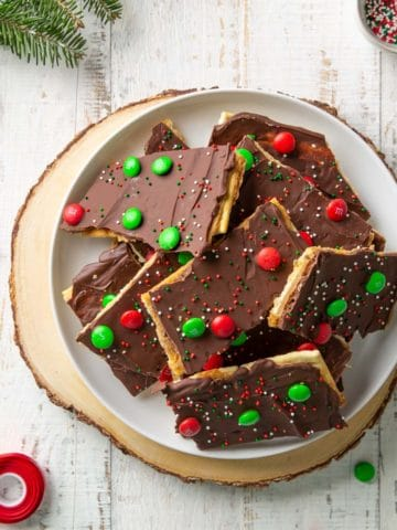 Overhead view of Christmas crack toffee candy on a white plate.