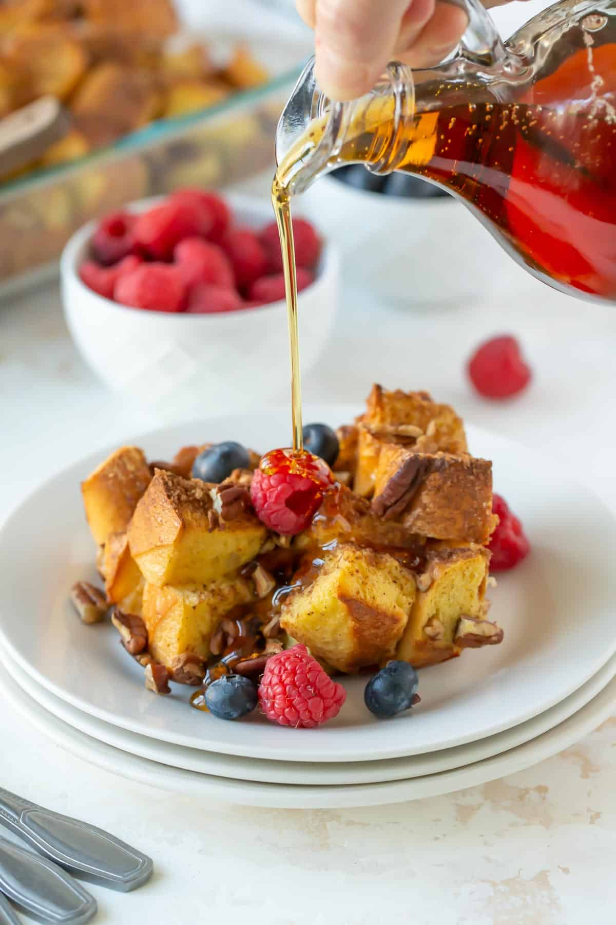 Syrup being poured over baked eggnog French toast with fruit in a white plate.