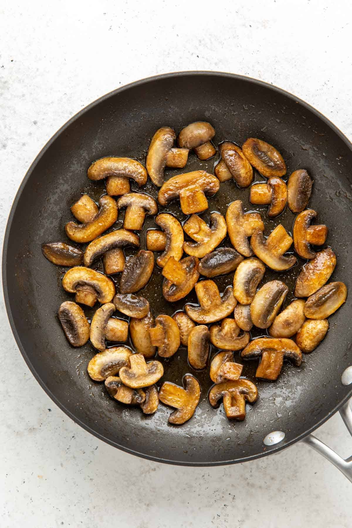 Overhead view of sauteed sliced mushrooms in a skillet.