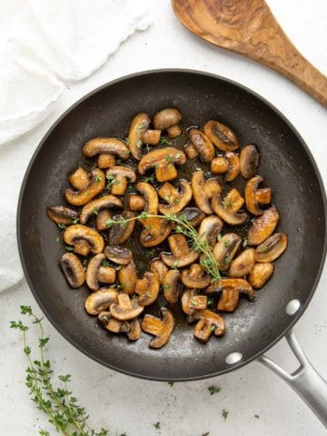 Overhead view of sauteed mushrooms garnished with fresh thyme in a skillet.
