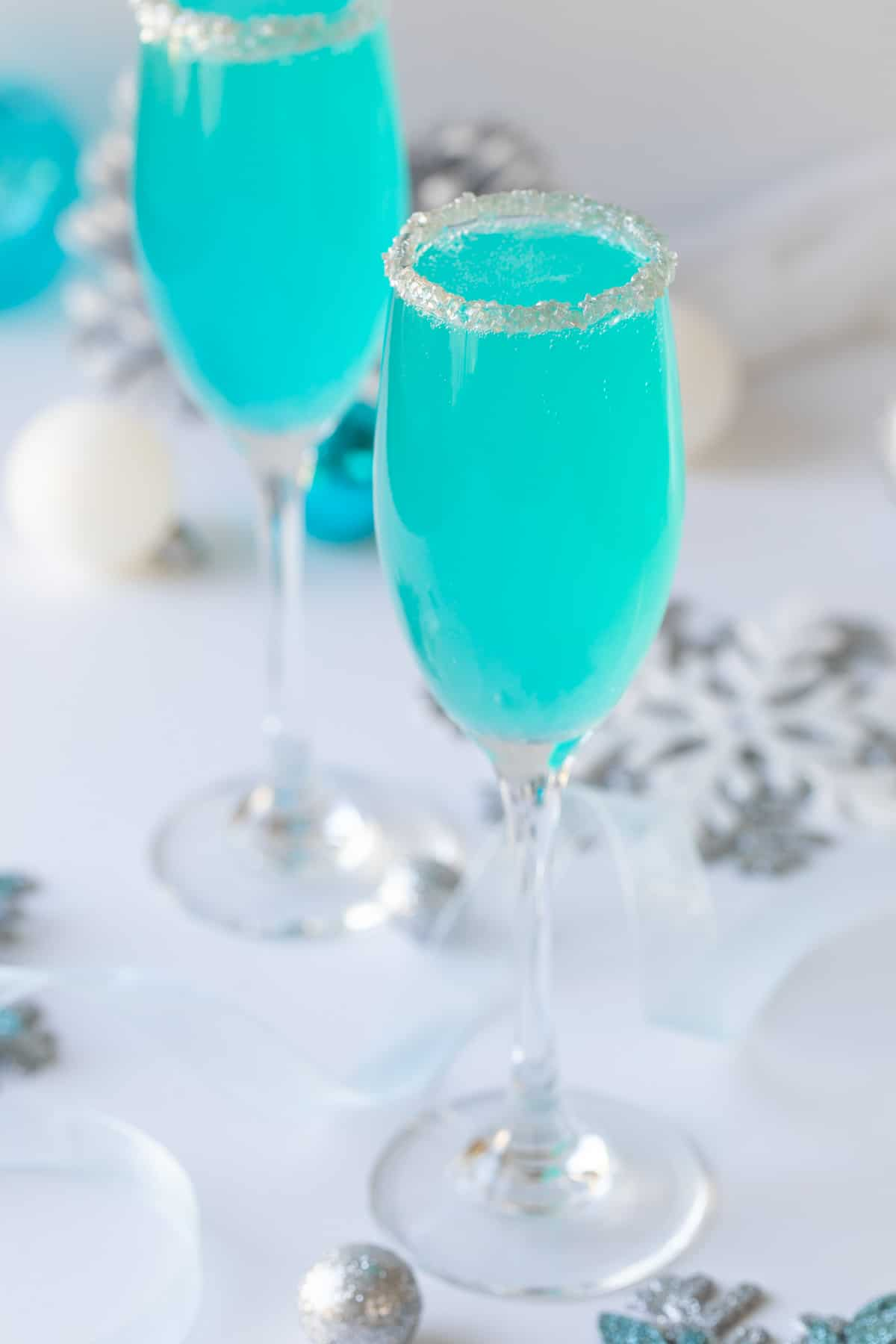Closeup view of a Tiffany blue mimosa in a champagne flute rimmed with sugar.