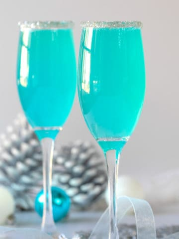 Two Tiffany blue mimosas in champagne flutes rimmed with sugar.