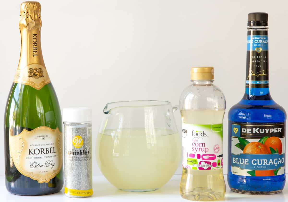 Front view of a bottle of champagne, sugar, lemonade, corn syrup and blue curacao.
