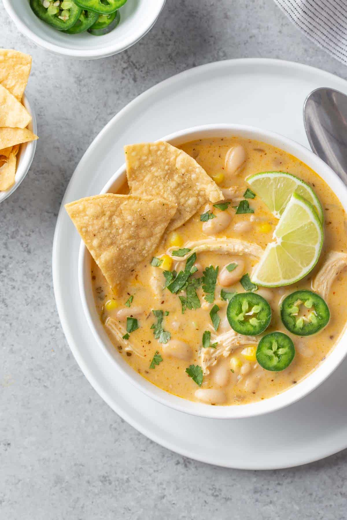Overhead view of a white bowl of white chicken chili with garnishes.