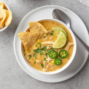 Overhead view of white chicken chili in a white bowl beside a spoon.
