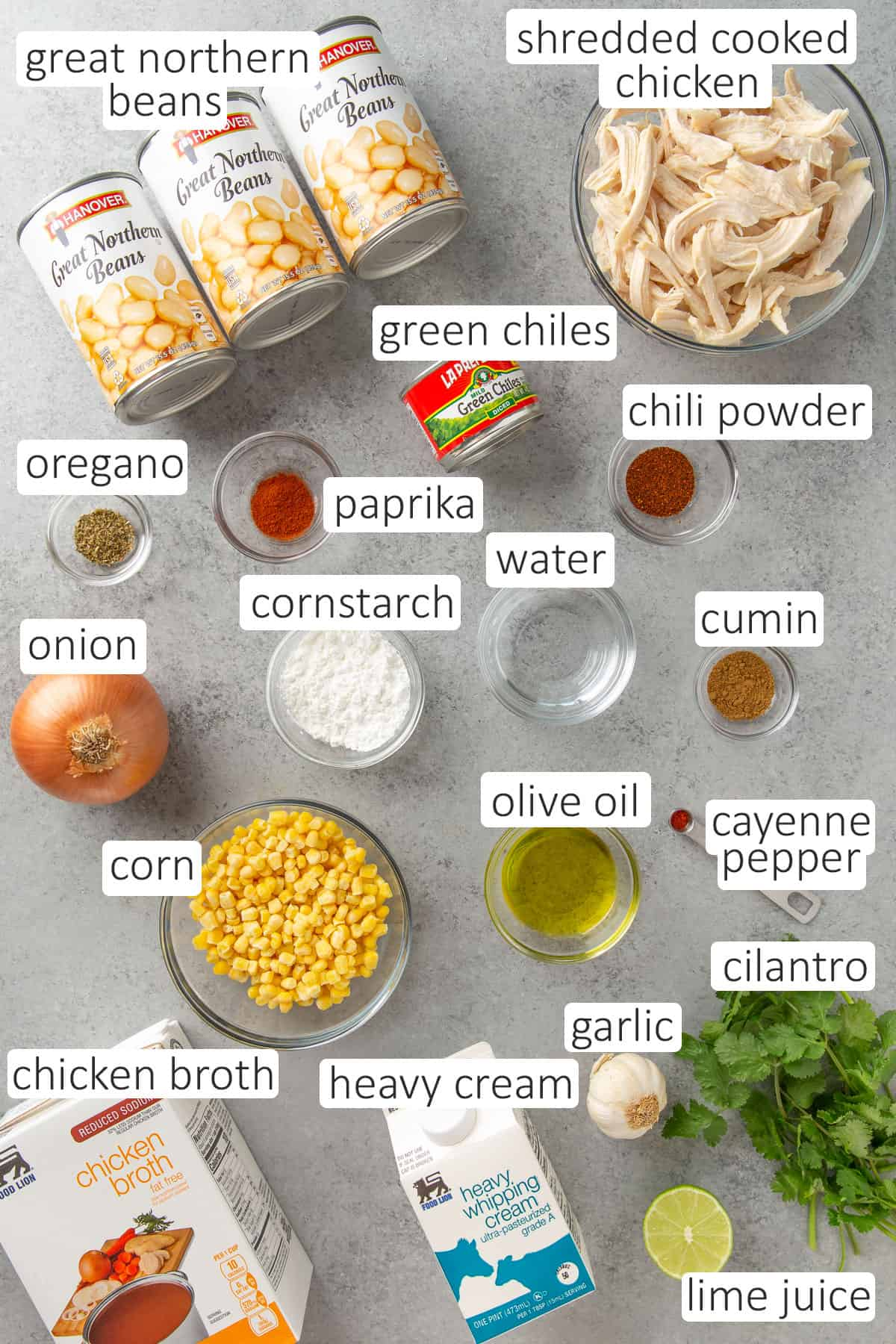 Overhead view of ingredients for white chicken chili on a gray surface.