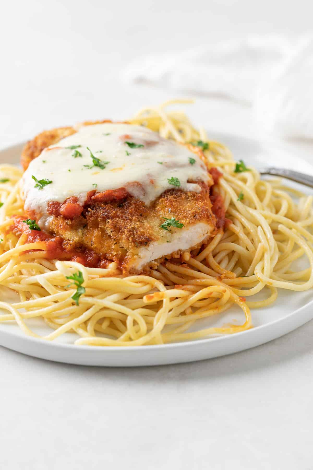 A closeup of classic chicken parmesan over a bed of pasta on a white plate.