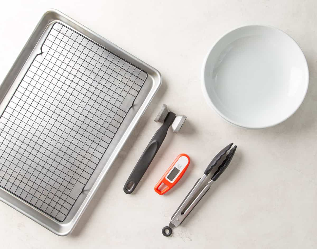 A cooling rack over a baking sheet, bowls, tongs, thermometer and a meat mallet.