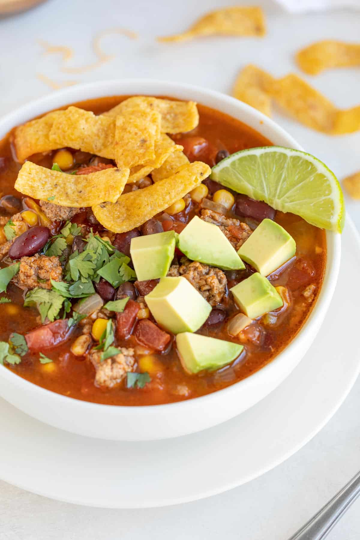 Closeup view of a white bowl of taco soup with toppings.