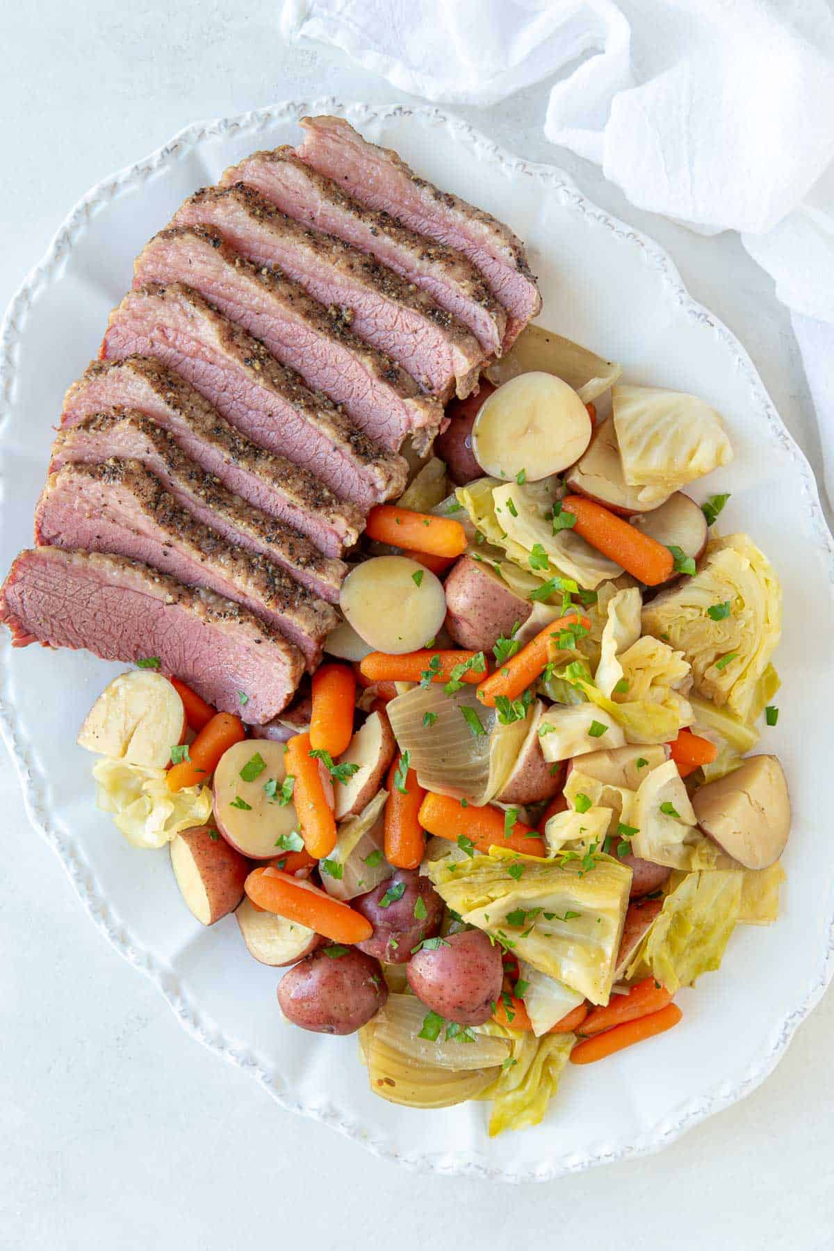 Overhead view of corned beef with cabbage, potatoes, onions and carrots on a white platter.