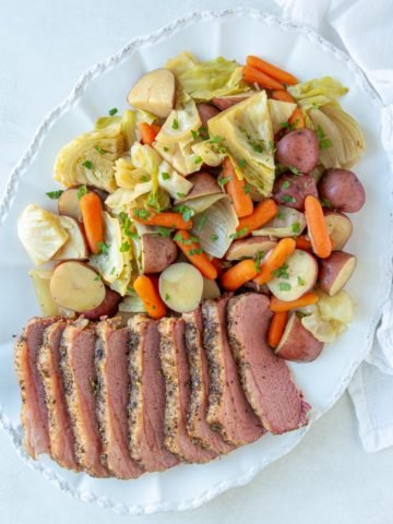 Overhead view of corned beef and cabbage on an oval white platter.