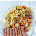 Sliced corned beef and vegetables on a white platter with overlay text.