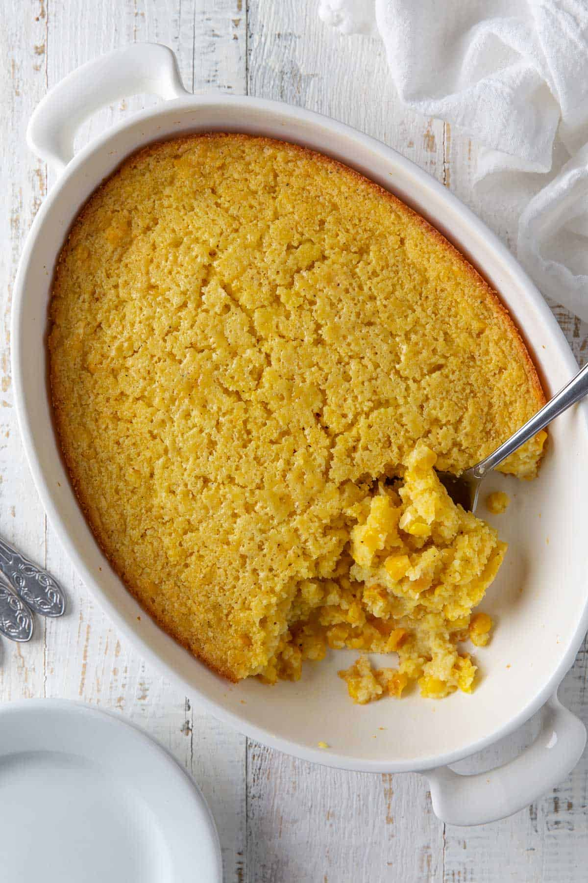 Jiffy corn pudding in an oval white baking dish with a serving spoon.