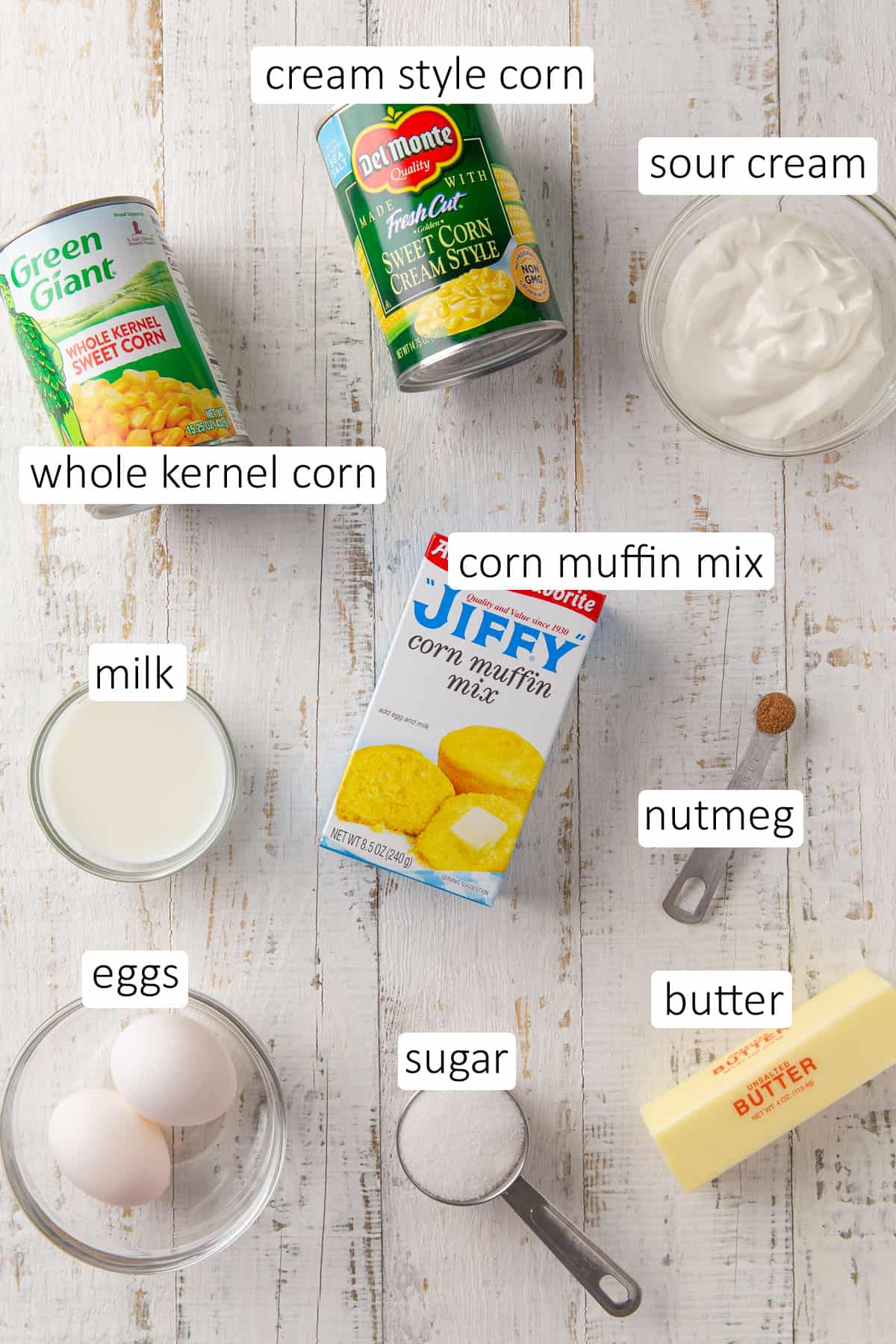 Overhead view of jiffy corn pudding ingredients on a white wood surface.