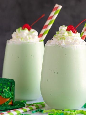 Two boozy shamrock shakes topped with whipped topping, sprinkles and cherries.
