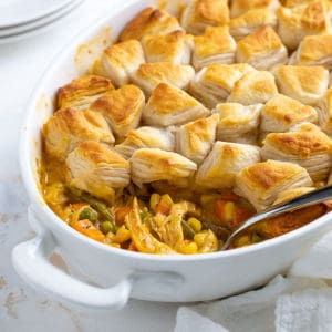 Cheesy chicken pot pie in a white dish with a spoon.