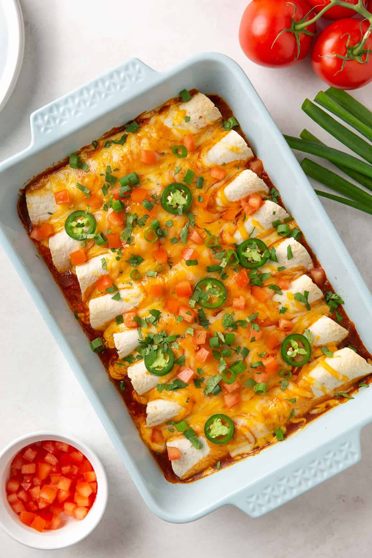 Overhead view of easy beef enchiladas in a light blue baking dish.