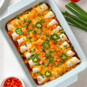 Overhead view of easy ground beef enchiladas in a baking dish.