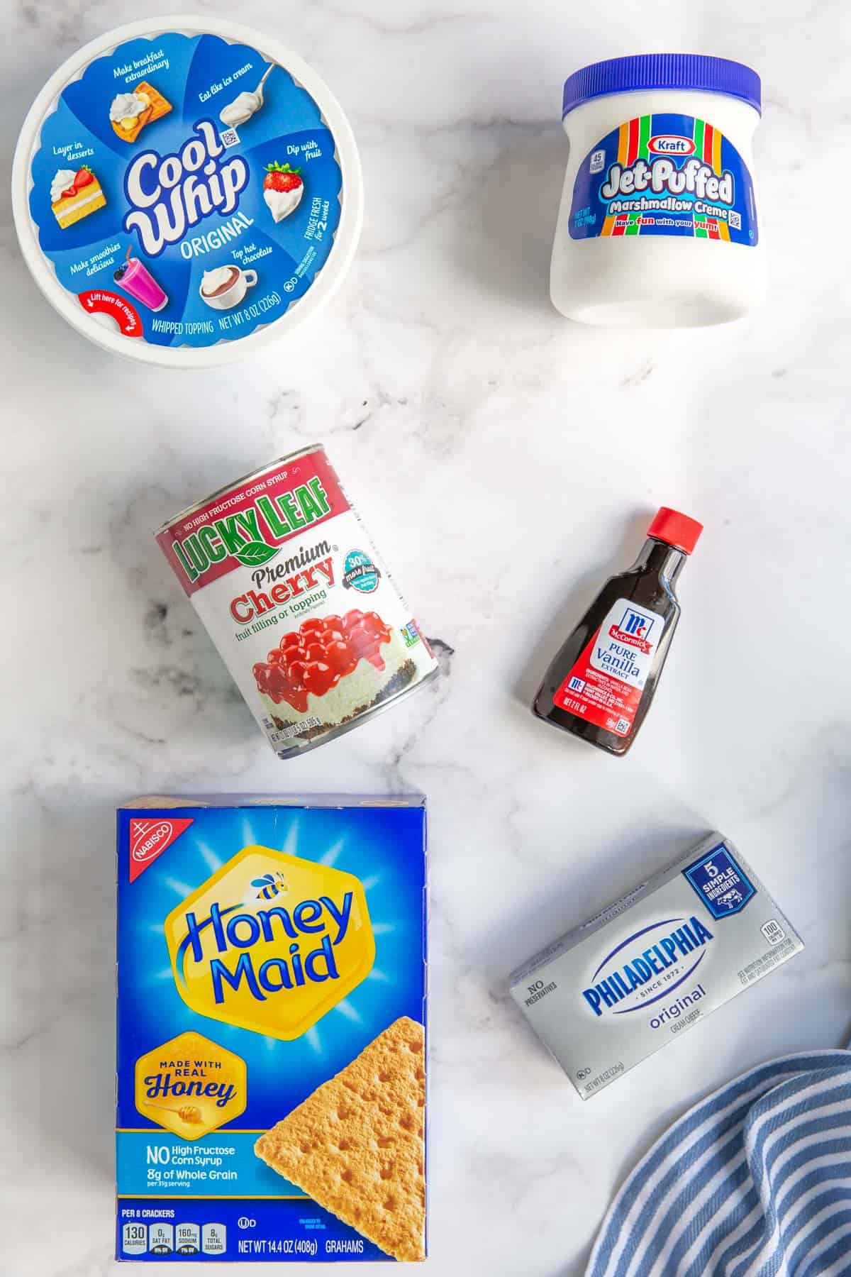Overhead view of ingredients for no bake cheesecake dip on a white marble surface.
