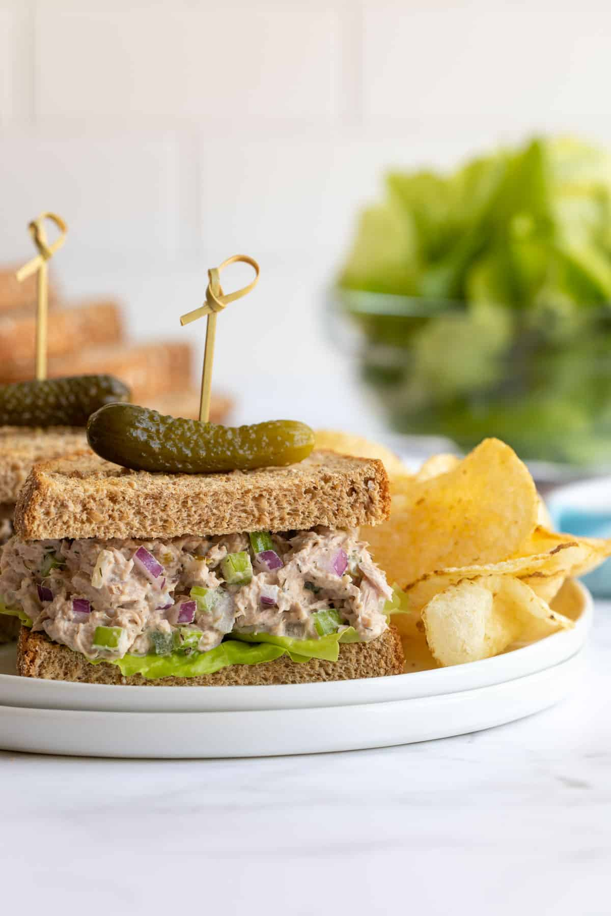 Front view of a classic tuna salad sandwich on a plate with potato chips.