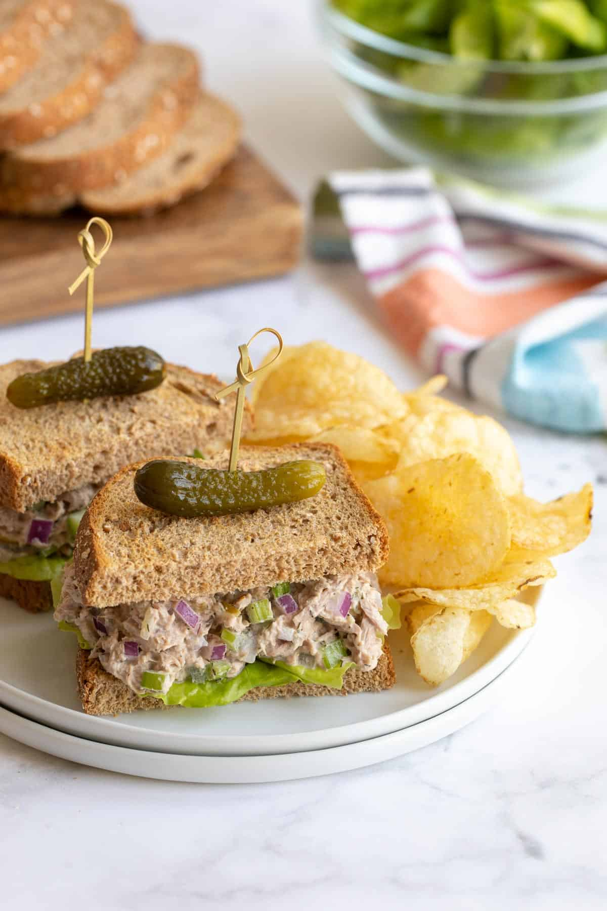 A sliced tuna salad sandwich on a white plate with potato chips.