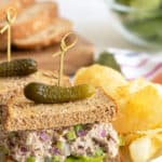 A closeup view of a tuna fish salad sandwich on a plate with overlay text.