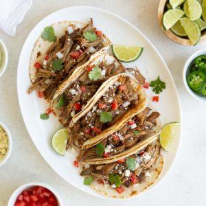 Five garnished instant pot pork carnitas tacos on a white oval platter.