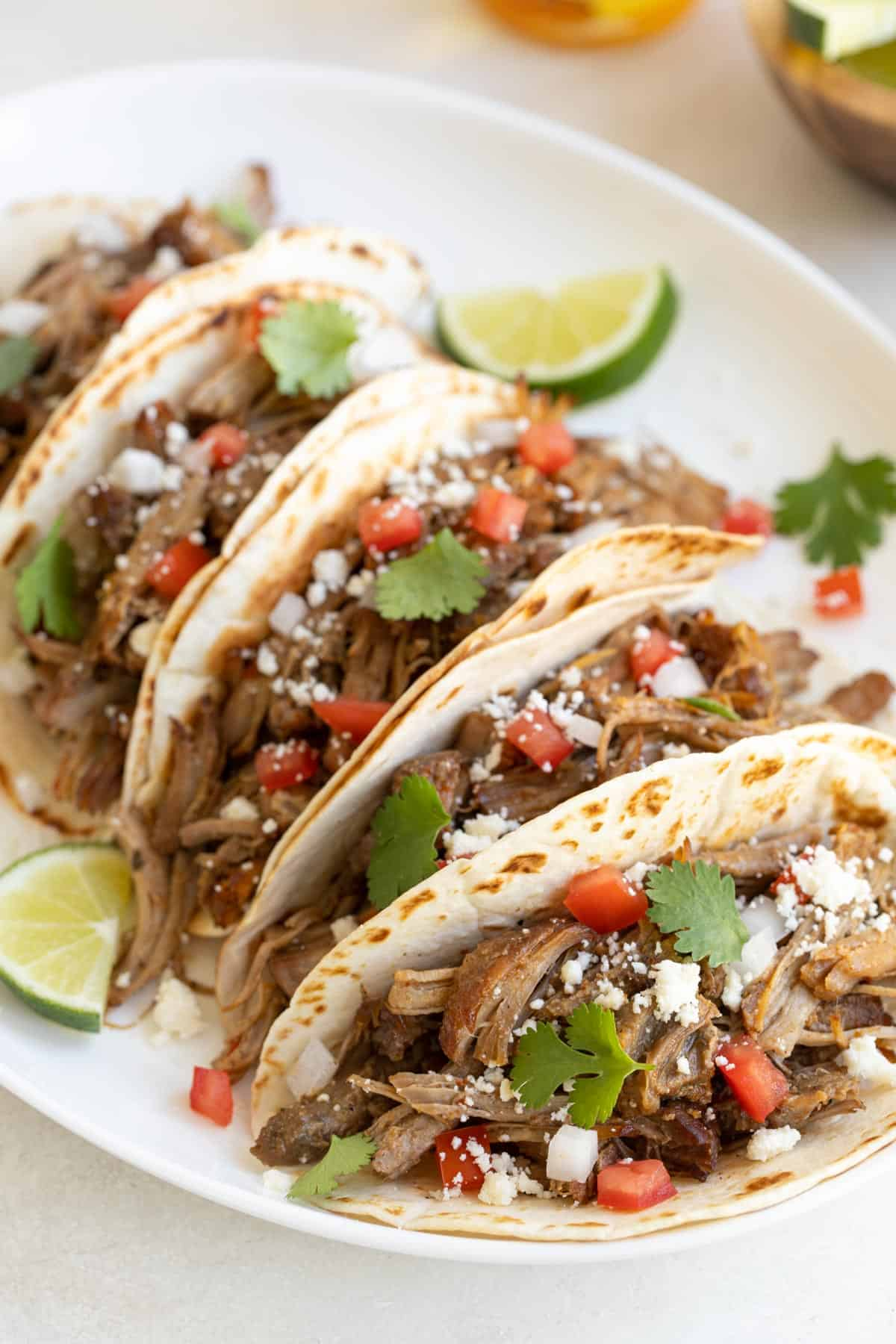 A closeup of instant pot carnitas tacos with toppings on an oval white platter.