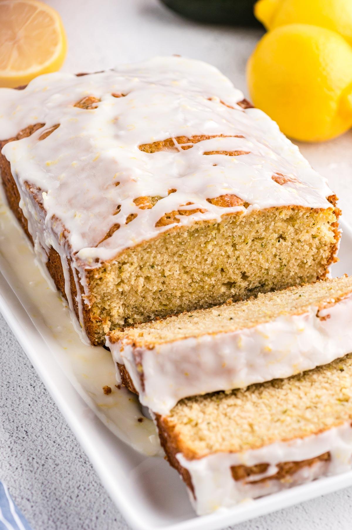 A closeup view of sliced lemon zucchini bread on a white platter.