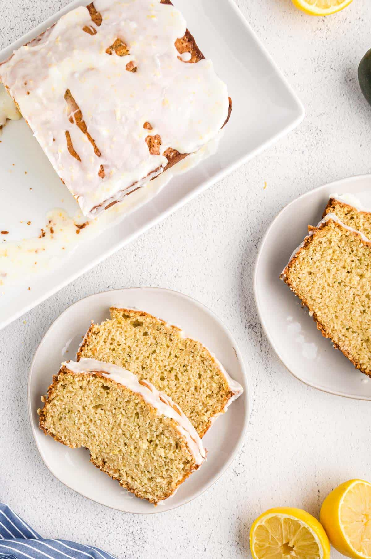 Overhead view of slices of lemon zucchini bread on two white dessert plates.