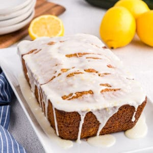 Front view of a glazed loaf of lemon zucchini bread on a white platter.