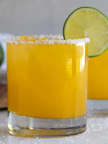 Front view of a garnished mango margarita on the rocks.