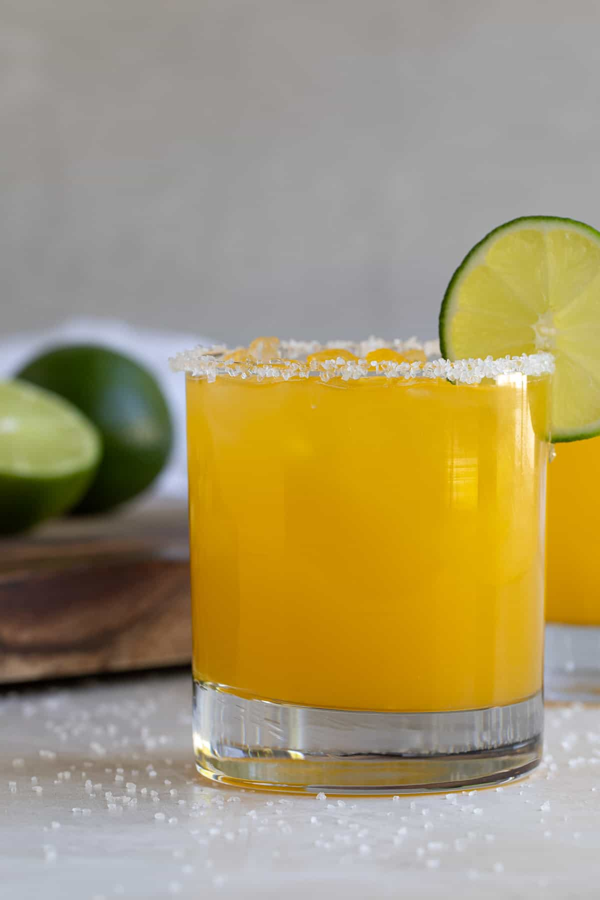 Front closeup view of a mango margarita garnished with lime.