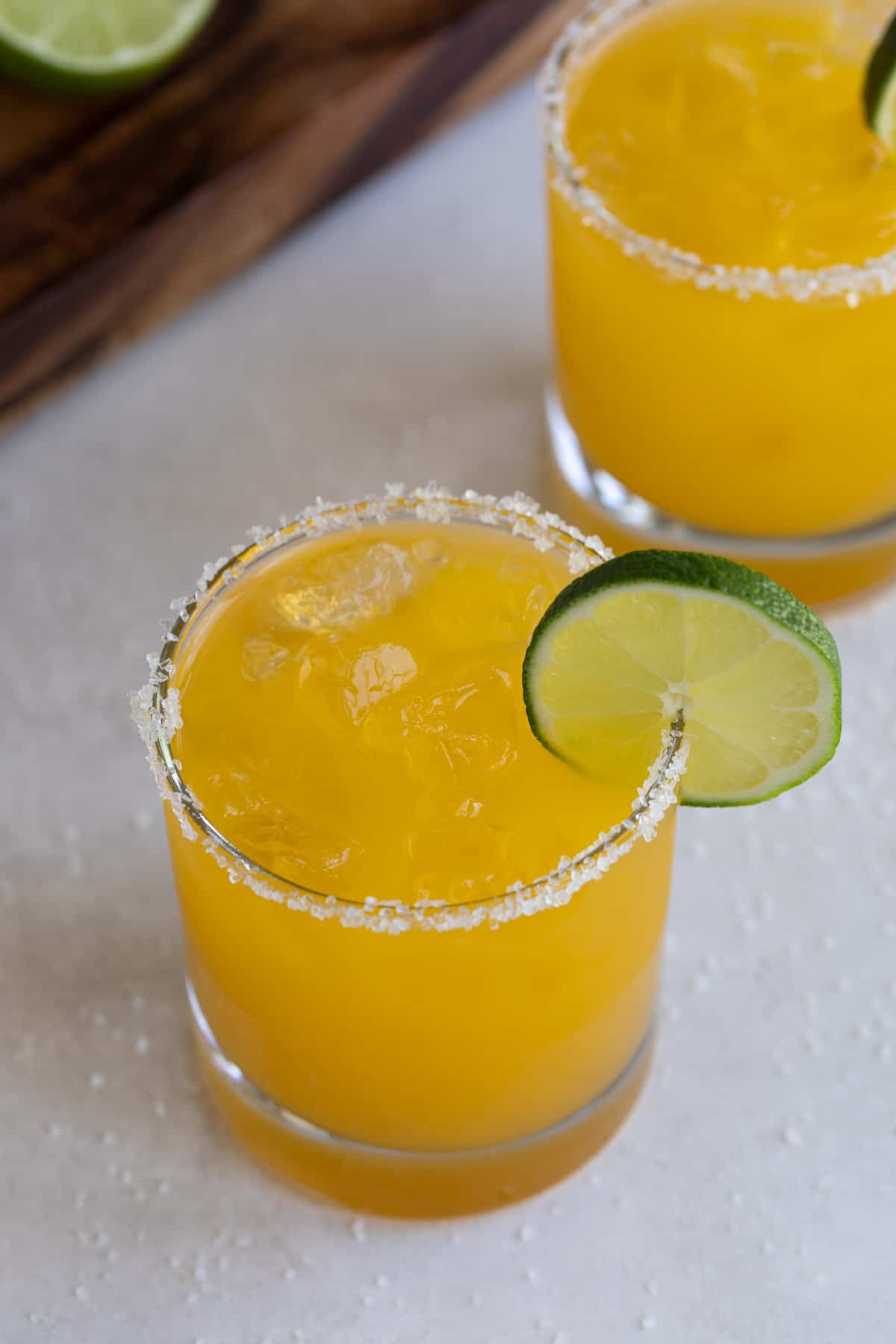 Two mango margaritas on the rocks garnished with lime wheels.