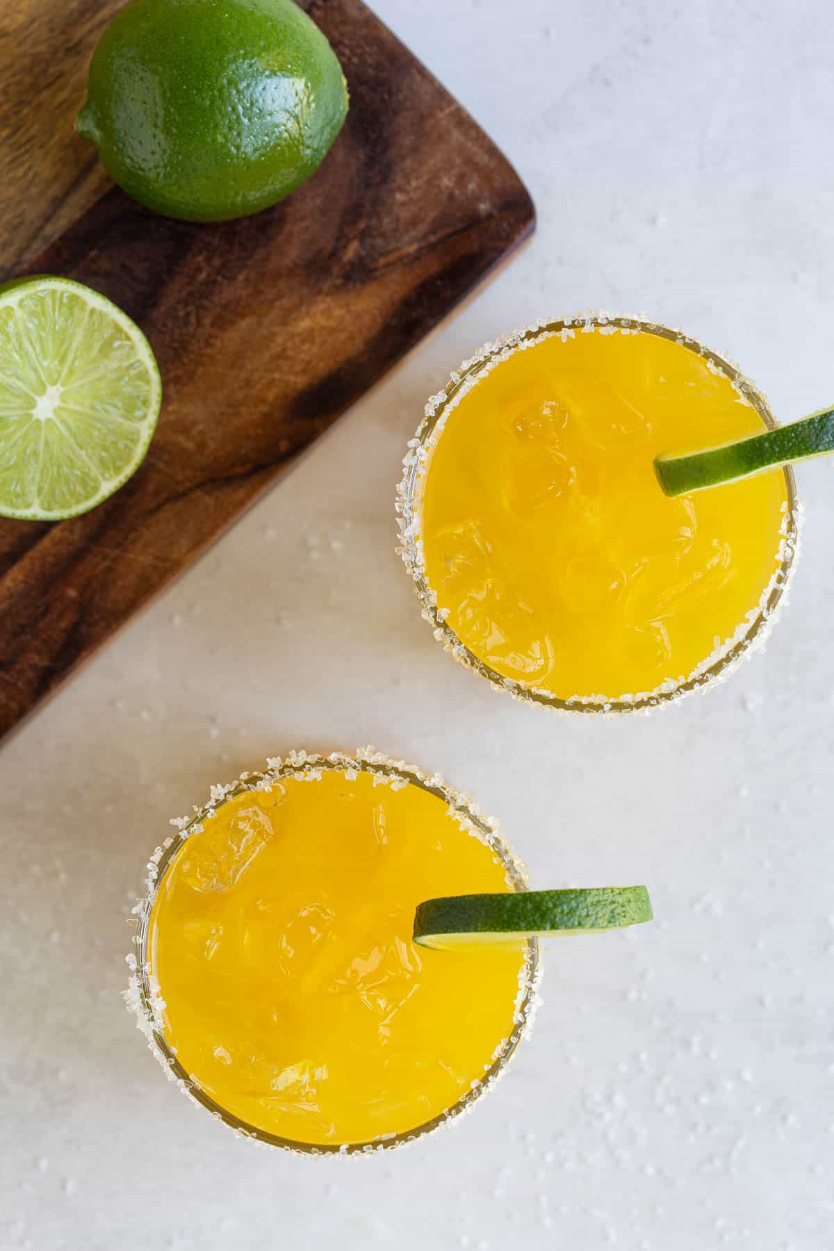 Overhead view of two mango margaritas garnished with lime wheels.