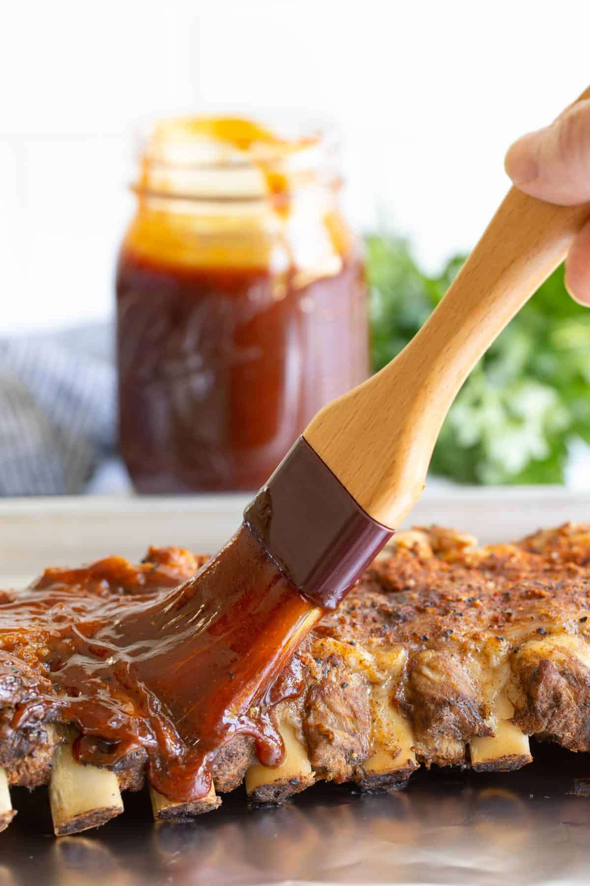 Brushing barbecue sauce on a rack of ribs on a baking sheet.