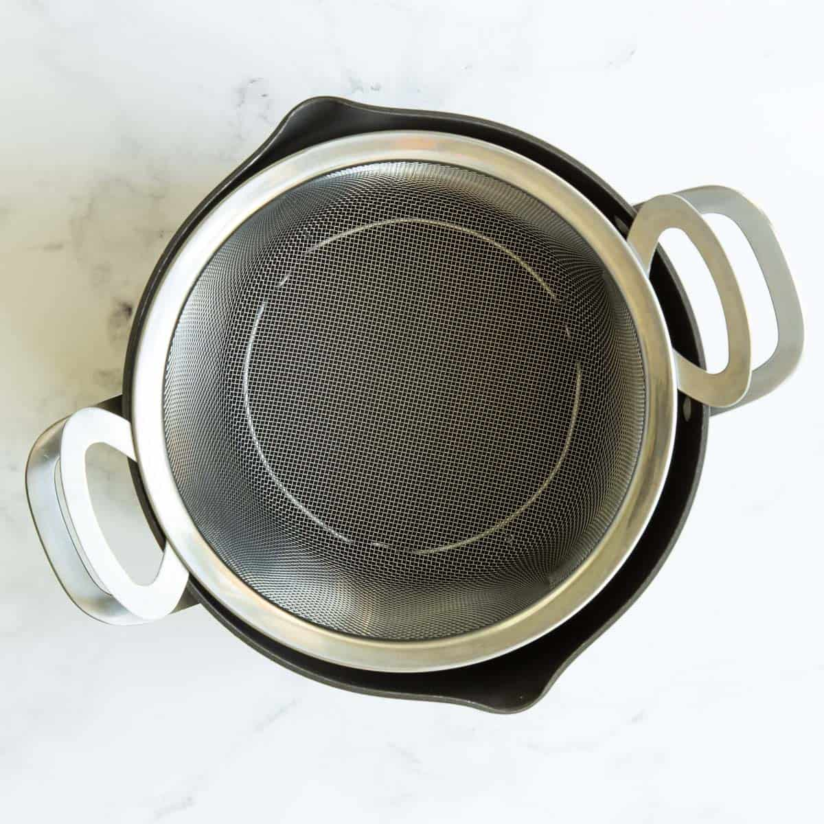 A stainless mesh strainer inserted into a pot to make a makeshift steamer basket.