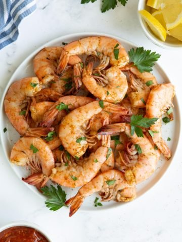 Overhead view of a plate of shrimp steamed with Old Bay Seasoning.
