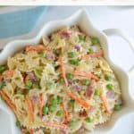 """Pasta salad in a square white bowl. Overlay text reads, """"pea pasta salad""""."""