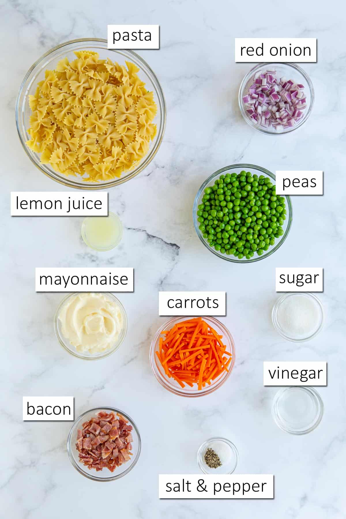 Overhead view of pea pasta salad ingredients on a white marble surface.