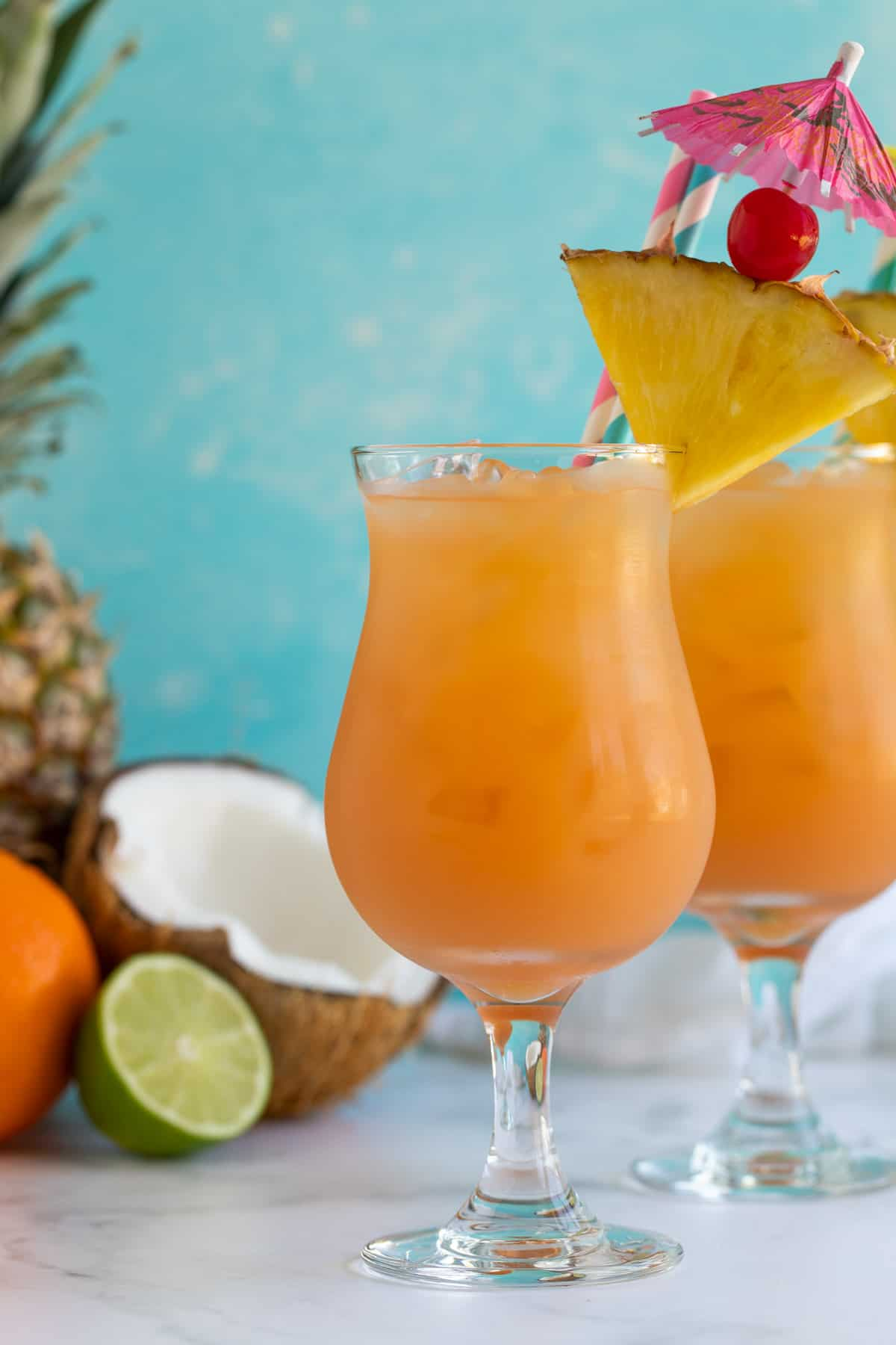 Two glasses of rum punch garnished with pineapple, cherries and umbrellas.