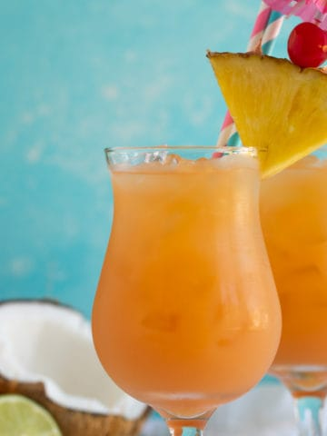 Front view of two glasses of rum punch with a blue background.