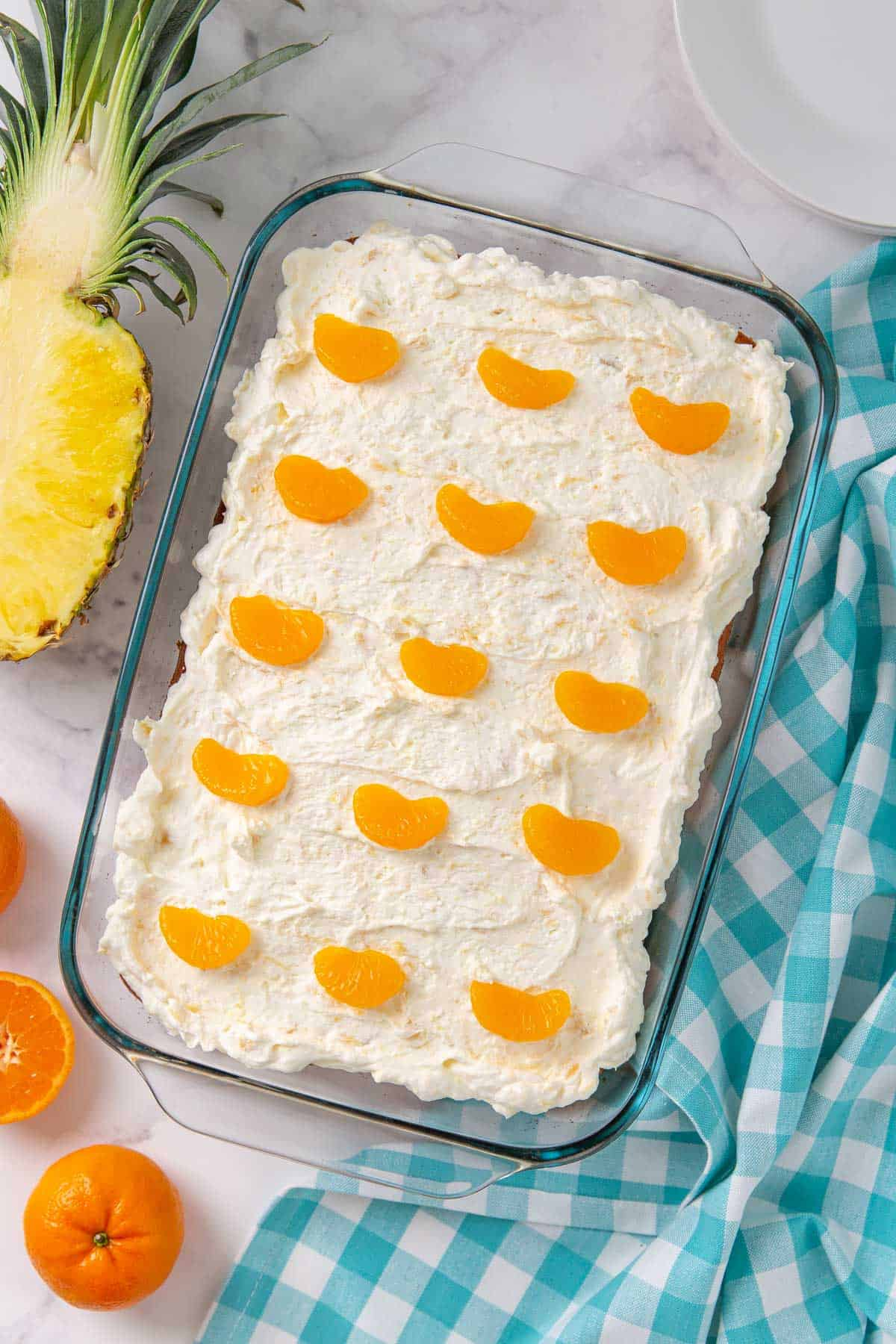 Overhead view of a pig pickin' cake by a  checked napkin, sliced pineapple and mandarin oranges.