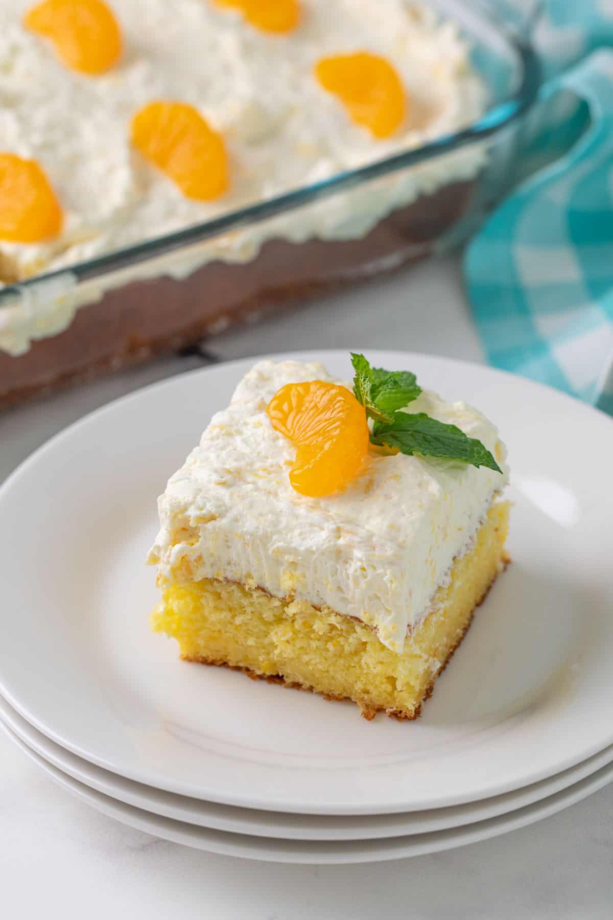 A slice of pig pickin' cake topped with a mandarin orange slice on a white plate.