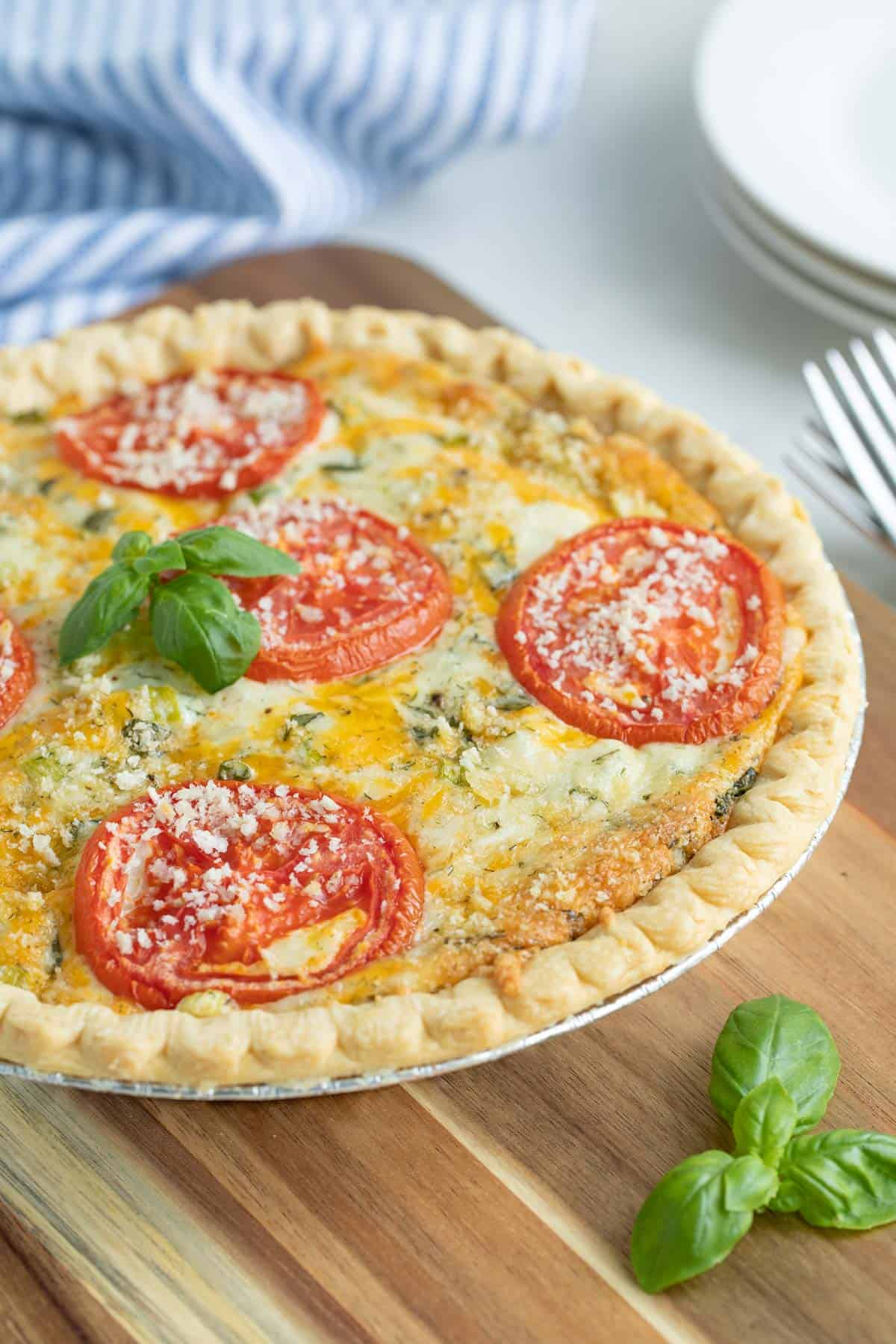 Front closeup view of a tomato pie topped with a sprig of fresh basil.