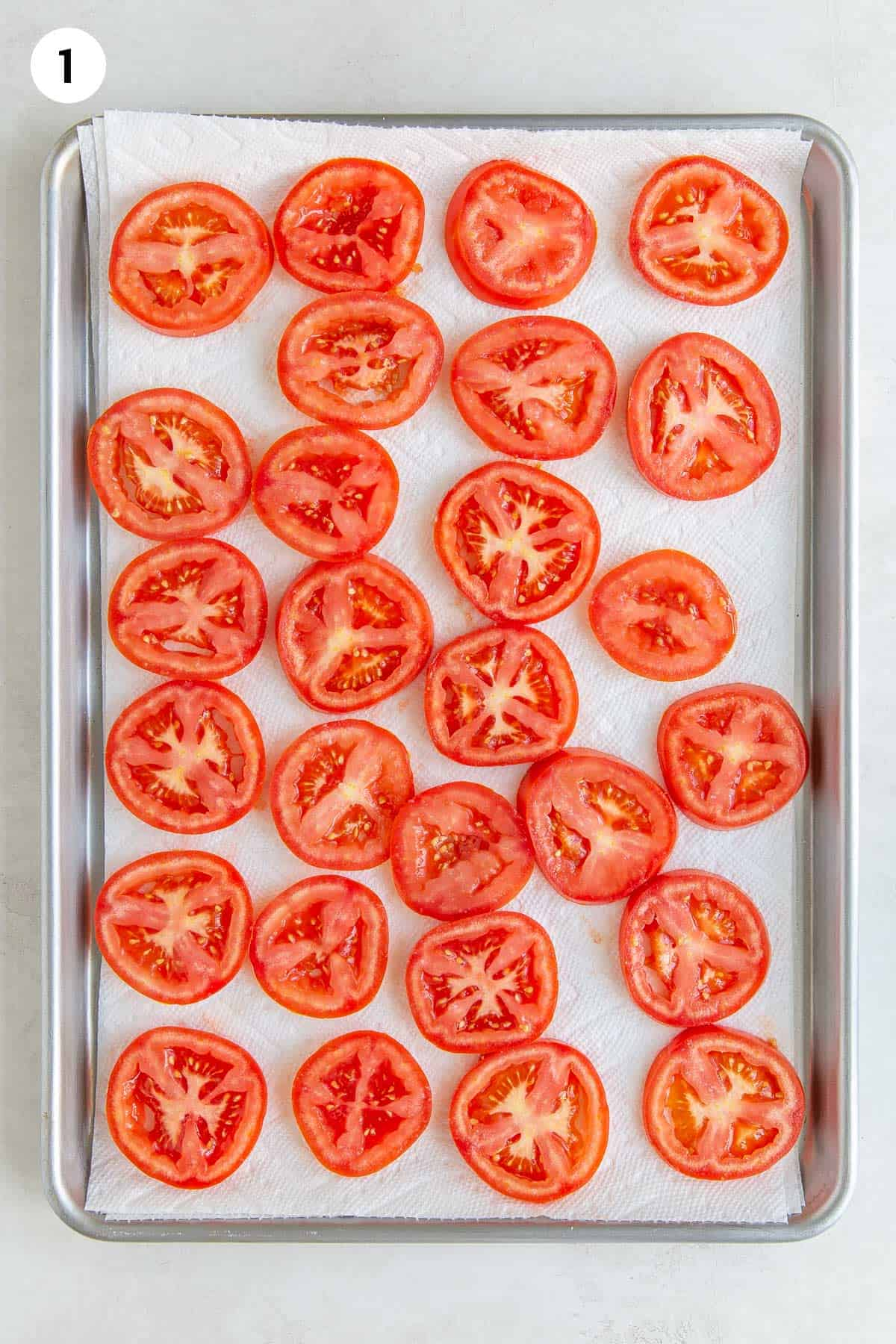 Overhead view of sliced tomatoes draining on paper towels on a baking sheet.