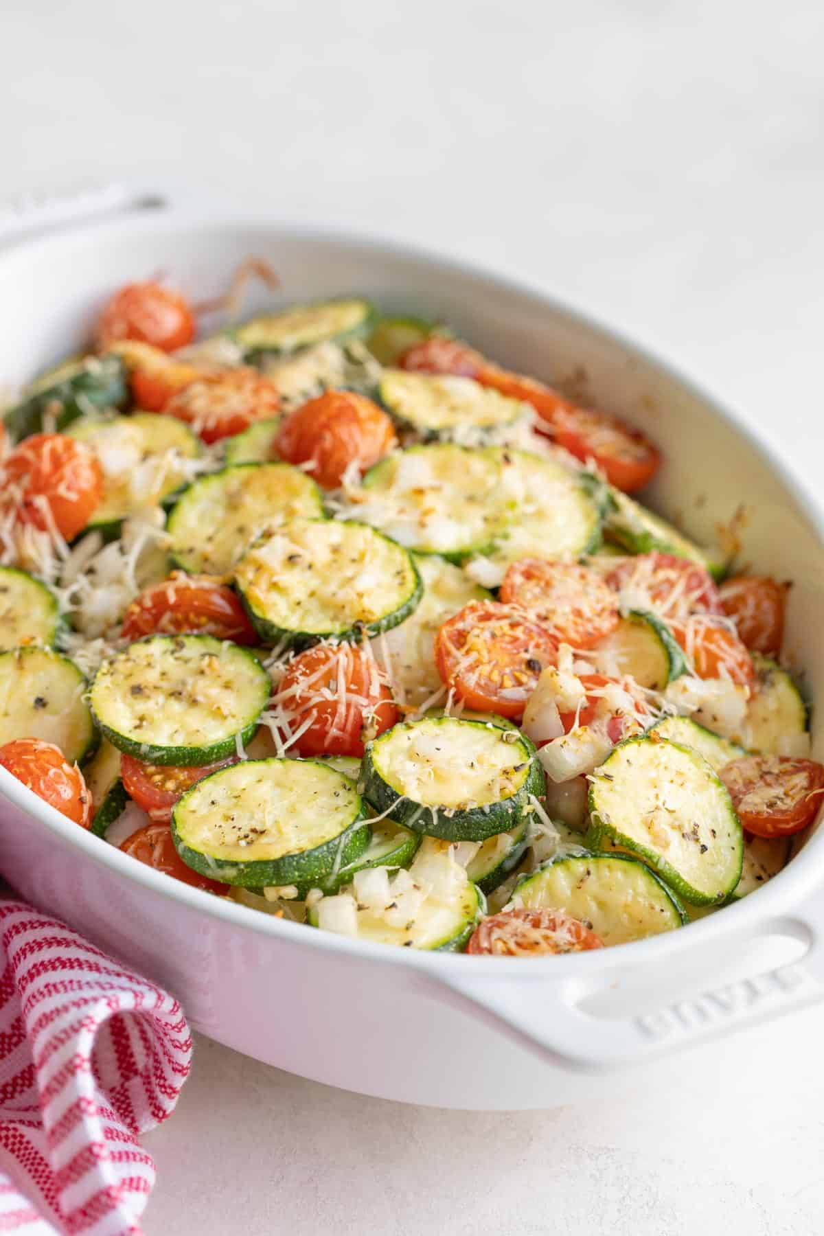 Front closeup view of zucchini tomato bake in a white baking dish.